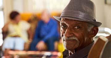 retraité noir souriant avec chapeau